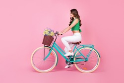 Full size profile side photo of positive cheerful girl ride retro bicycle collect field wild flowers wear green white outfit isolated over pastel color background