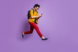 Full size profile side photo of positive hipster guy relax trip jump use smartphone search discounts run fast wear yellow shirt red pants rucksack isolated violet color background