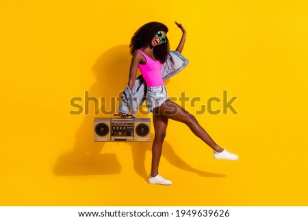 Full size profile side photo of young black girl happy smile have fun dance listen music boombox isolated over yellow color background Stockfoto ©