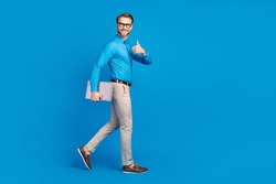Full size profile side photo of young man happy smile go walk show thumb-up advert advise laptop isolated over blue color background