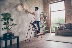 Full size profile view photo of mixed race guy installing wall shelf standing stepladder repair of new flat handmade working hanging last shelf checking sustainability flat indoors