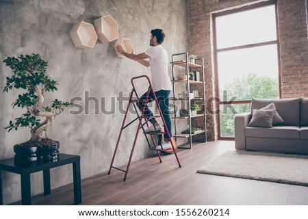 Full size profile view photo of mixed race guy installing wall shelf standing stepladder repair of new flat handmade working hanging last shelf checking sustainability flat indoors Foto stock ©