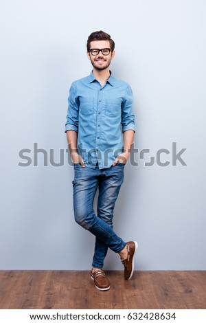 Full size vertical portrait of cheerful brunet young man in casual stylish wear. He looks at camera on lifgt background #632428634
