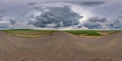 Full spherical seamless panorama 360 degree angle view on no traffic old asphalt road among fields with dark overcast sky before storm in equirectangular projection, VR AR content