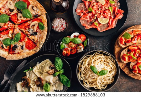 Full table of italian meals on plates Pizza, pasta, ravioli, carpaccio. caprese salad and tomato bruschetta on black background. Top view