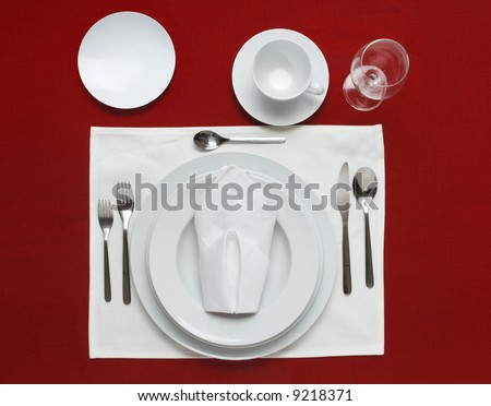 Full table place setting on a red table cloth