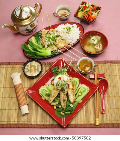 Full table setting of Asian chicken skewers with short soup and vegetables.