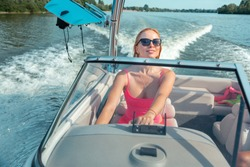 Full throttle ahead. Front view of a pleased sporty blonde girl in a pink tank top driving a speedboat across the river