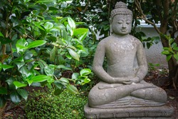 Full view meditative Buddha stone sculpture in the lotus position in a garden in front of green bushes