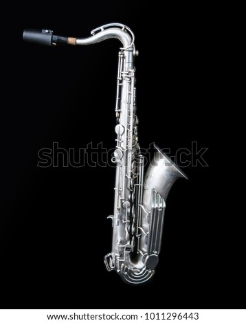 Full view of a silver saxophone isolated in black