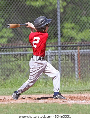 Full view of a young baseball player taking a major league swing at the ball.