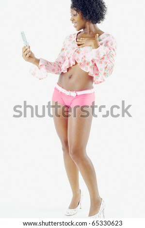 Full view of woman in short shorts holding cell phone