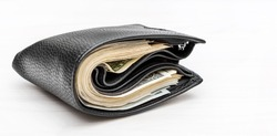 Full wallet with money on white wooden background.