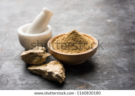 Fuller'S Earth Clay OR Multani mitti in a bowl along with raw stones and mortar