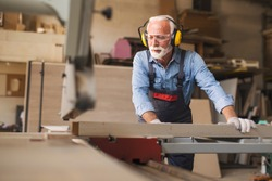 Fully equipped smiling senior carpenter operating on a woodworking machine