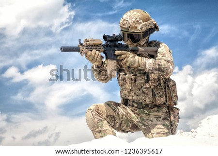 Fully equipped with tactical ammunition airsoft player in military camouflage uniform, aiming with optical sight on service assault rifle replica while stand on one knee at cloudy sky background