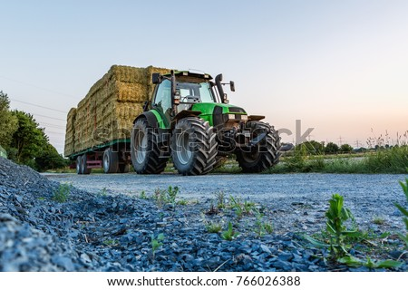 Fully loaded, green tractor with trailer transports straw bales. In the foreground is a pile of gravel stones.