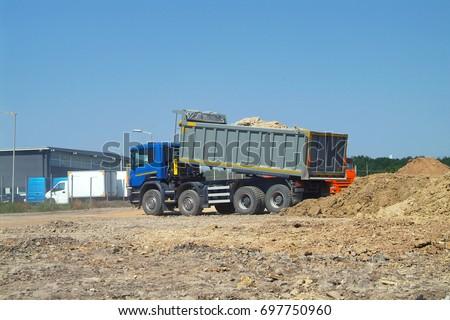 Fully Loaded Modern Dump Truck Unloading Soil On Construction Site