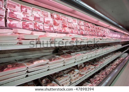 Fully loaded shelves with meat in a large supermarket