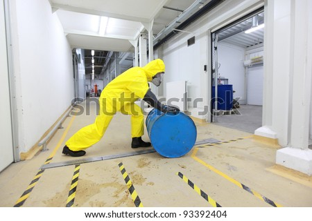 fully protected in yellow uniform,mask,and rubber gloves and boots worker,rolling the barrel with toxic substance