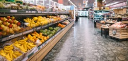 Fully stocked aisles in a grocery store. Assorted fruits and vegetables on racks in supermarket.