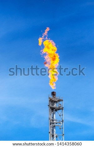 fume of fire on flare stack to burning heat gas, pollution in environment, for power and safety in petrochemical, chemical refinery or power plant in industrial zone, blue sky, global warming concept #1414358060