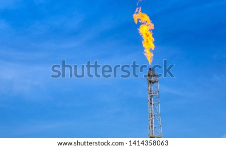 fume of fire on flare stack to burning heat gas, pollution in environment, for power and safety in petrochemical, chemical refinery or power plant in industrial zone, blue sky, global warming concept #1414358063