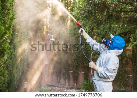 Fumigator applying plant protection products and herbicides to the plants of a house with a garden. The fighter is wearing a protective mask and a white protective suit against toxic products.