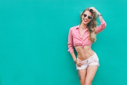 Fun and colorful. Young pretty happy woman in shorts posing against green wall.