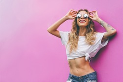 Fun and colorful. Young pretty happy woman in shorts posing against pink wall.