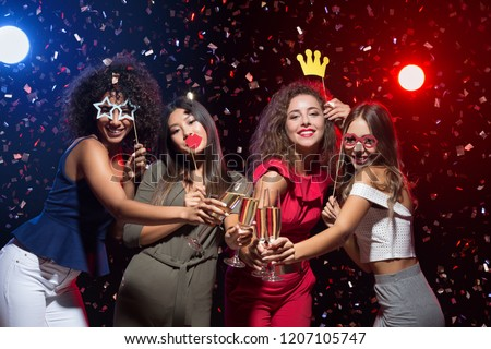 Fun at New Year party. Happy women celebrating and posing with photo props and champagne #1207105747