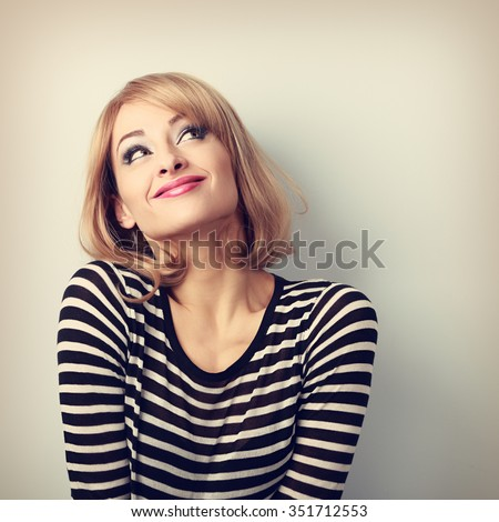 Fun beautiful thinking blond young woman in sweater looking up. Vintage toned portrait #351712553