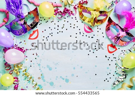 Fun carnival, masquerade or Mardi Gras frame with bright metallic masks with feathers above red lips on a light blue textured background with copy space, streamers and confetti