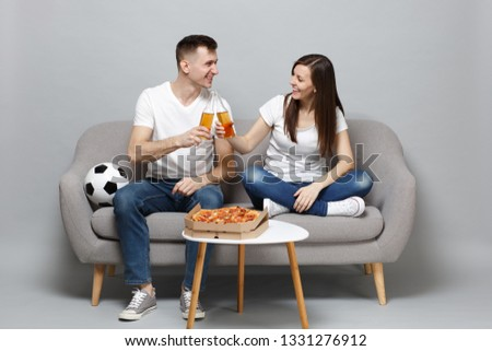 Fun cheerful couple woman man football fans cheer up support favorite team with soccer ball, holding beer bottles isolated on grey background. People emotions, sport family leisure lifestyle concept #1331276912