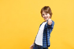 Fun cheerful happy little kid boy in blue shirt white t-shirt posing gesturing hands isolated on yellow background children studio portrait. People childhood lifestyle concept. Mock up copy space