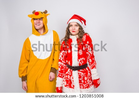 Fun, Christmas and holidays concept - happy woman in santa clothes with man in costume of deer are dancing over the white background