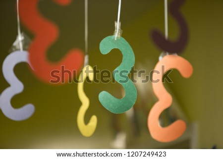 Fun colorful threes numbers cutouts and hanging by a string from the ceiling as hallway mobile decorations. #1207249423