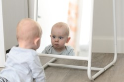 Fun cute baby seeing self in mirror
