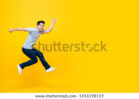 Fun energetic young handsome Asian man jumping in mid-air studio shot isolated on yellow background with copy space