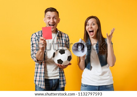 Fun expessive crazy couple, woman man football fans screaming, cheer up support team with soccer ball, megaphone, red card isolated on yellow background. Sport family leisure lifestyle concept