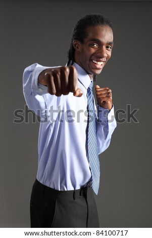 Fun fighting punch from handsome young African American businessman standing wearing black suit trousers and blue shirt and neck tie. He has short dreadlocks and a big happy smile.