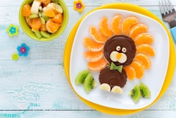 Fun Food for Kids - cute lion shaped sweet toast with chocolate spread and fresh fruits like kiwi, tangerine and banana served with a glass of milk and biscuits for breakfast