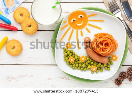 Fun food for kids - Cute little snail made of spaghetti and a sausage, served with green peas and cheddar cheese decoration