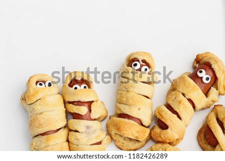 Photo of Fun food for kids. Halloween mummy hot dogs.  Wieners wrapped in croissant rolls to look like mummies on a plate. Alternative to candy.