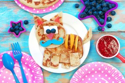 Fun food for kids. Tiger shaped pancakes on blue wooden table, top view. Healthy eating for children. Creative idea for kids breakfast.