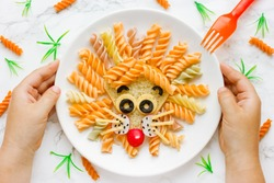 Fun food idea for kids lunch, animal shaped food art - colorful fusilli vegetables pasta with sandwich like a cute lion head on white plate top view