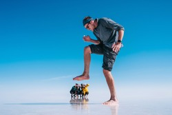 Fun forced perspective shot of young tourists at Uyuni Salt Flats (Spanish: Salar de Uyuni ) in Bolivia, South America.