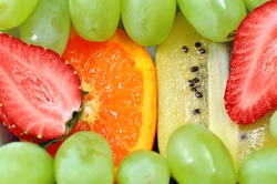 Fun fruit mix background with green grapes, strawberries, kiwi and oranges, focus on the orange and kiwi.