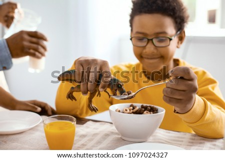 Fun game. Charming upbeat boy playing with a toy dinosaur being in the focus and feeding it with cereals while having breakfast himself