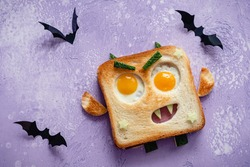 Fun Halloween monster sandwich with slice meat sausage, eggs and cheese on plate